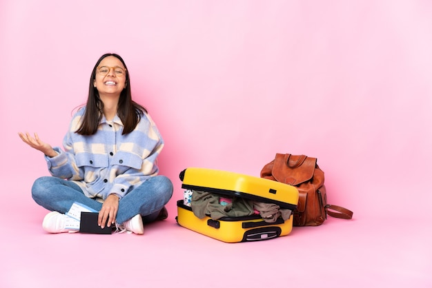 Kobieta podróżnik z walizką, siedząc na podłodze, dużo uśmiechając się