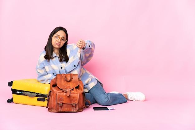 Kobieta podróżnik z walizką, siedząc na podłodze, pokazując kciuk w dół z negatywnym wyrazem twarzy