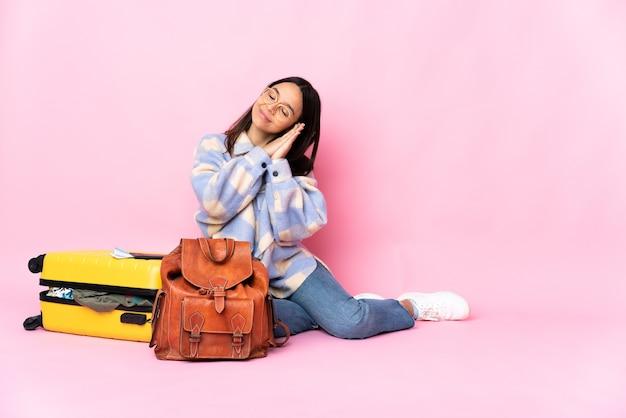 Kobieta podróżnik z walizką, siedząc na podłodze, robiąc gest spania w dorable wypowiedzi