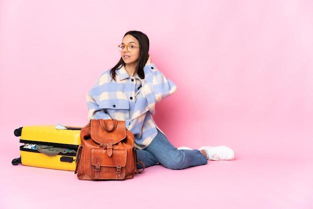 Kobieta podróżnik z walizką, siedząc na podłodze w tylnej pozycji i myśląc