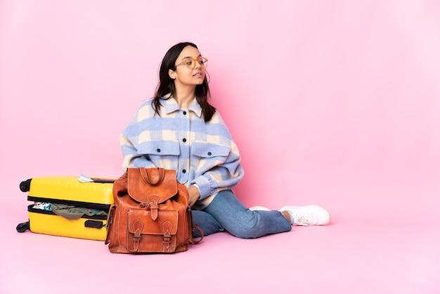 Kobieta podróżnik z walizką, siedząc na podłodze w tylnej pozycji i patrząc z boku