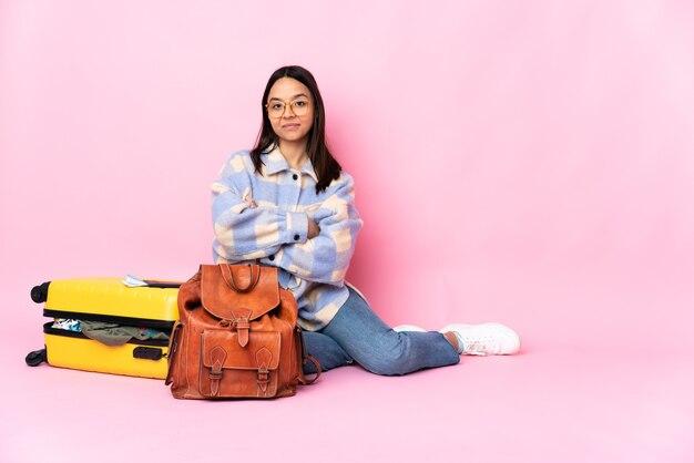 Kobieta podróżnik z walizką, siedząc na podłodze w tylnym położeniu