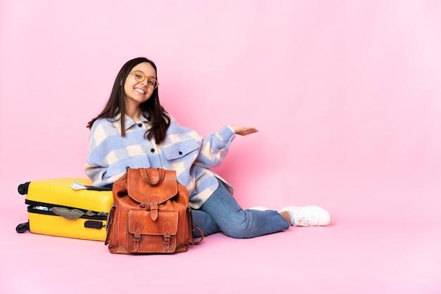 Kobieta podróżnik z walizką, siedząc na podłodze, wyciągając ręce