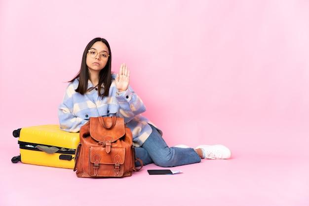 Kobieta podróżnik z walizką, siedząc na podłodze, wykonując gest stopu