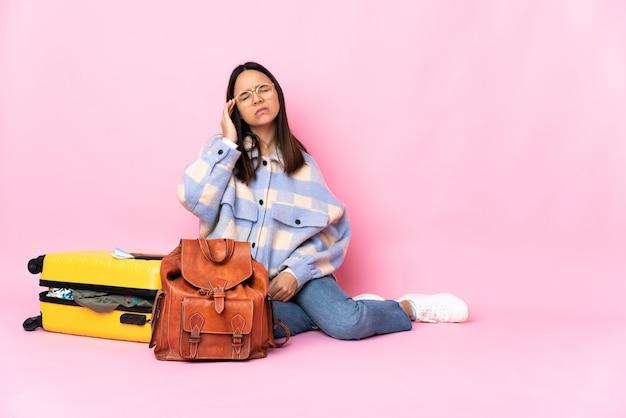 Kobieta podróżnik z walizką, siedząc na podłodze z bólem głowy