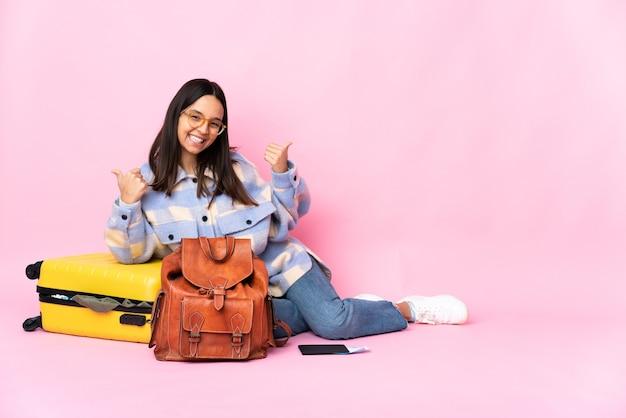 Kobieta podróżnik z walizką, siedząc na podłodze z kciuki gest i uśmiechnięty
