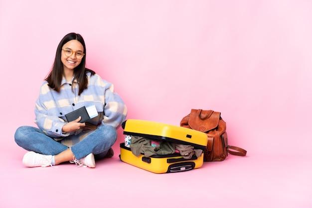Kobieta podróżnik z walizką, siedząc na podłodze z rękami na biodrze i uśmiechając się