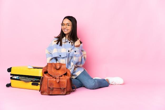 Kobieta podróżnik z walizką, siedząc na podłodze, zarabianie pieniędzy gestem
