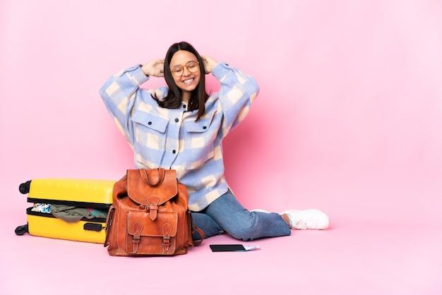 Kobieta podróżnik z walizką, siedząc na podłodze ze śmiechu