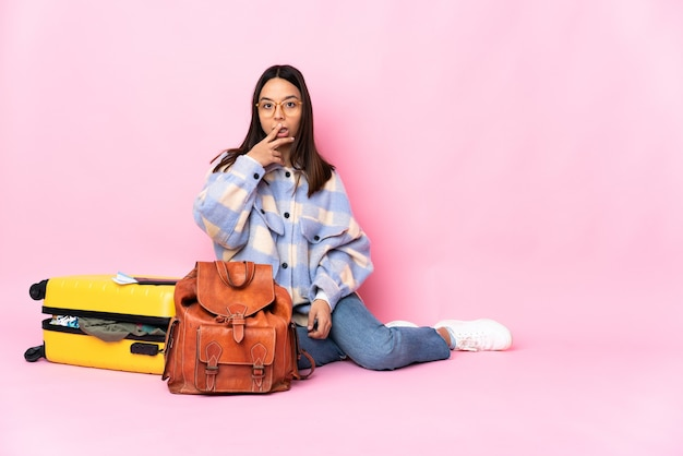 Kobieta podróżnik z walizką, siedząc na podłodze