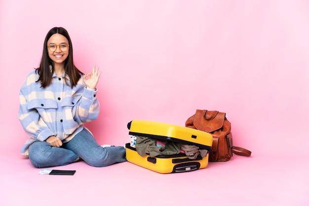 Kobieta podróżnik z walizką siedzi na podłodze, pokazując znak ok palcami
