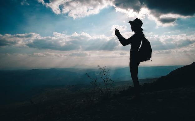 Kobieta podróżnika pozycja na górze góry i brać fotografia widok natura na wakacje.