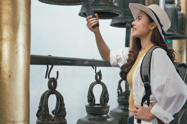 Kobieta podróżnika pukania turystyczny dzwon w świątyni. podróż podróż podróż
