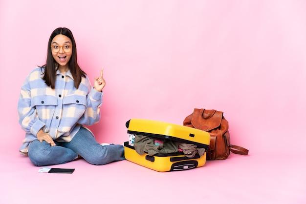 Kobieta podróżnika z walizką na podłodze, skierowana w górę i zaskoczona