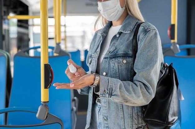 Kobieta podróżująca autobusem publicznym, używająca środka dezynfekującego do rąk, mając na sobie maskę medyczną dla ochrony