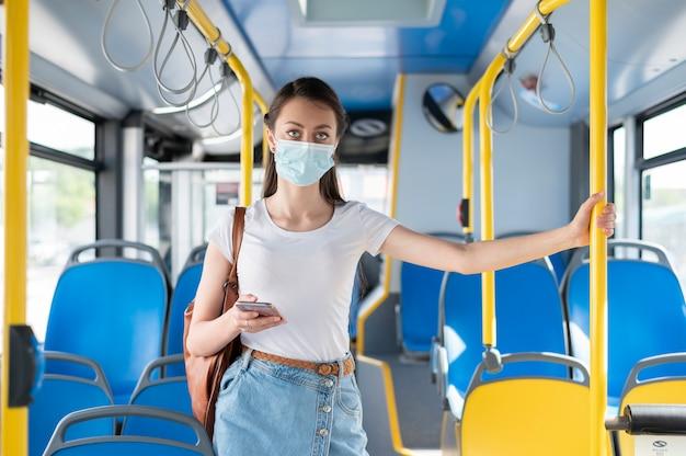 Kobieta podróżująca autobusem publicznym za pomocą smartfona z maską medyczną dla ochrony
