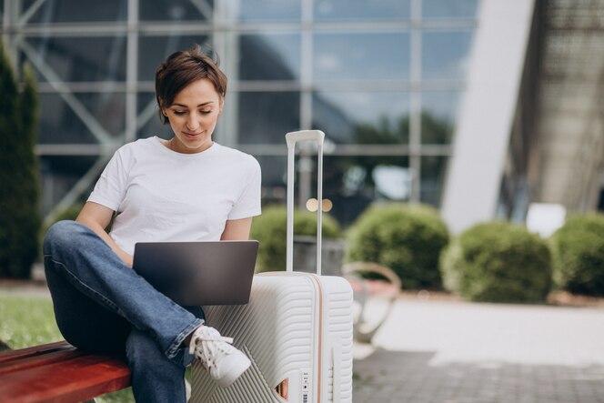 Kobieta podróżująca i pracująca na komputerze na lotnisku