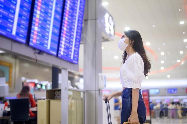 Kobieta podróżująca nosi maskę ochronną na międzynarodowym lotnisku, podróżuje w czasie pandemii covid-19, podróże bezpieczeństwa, protokół dystansowania się