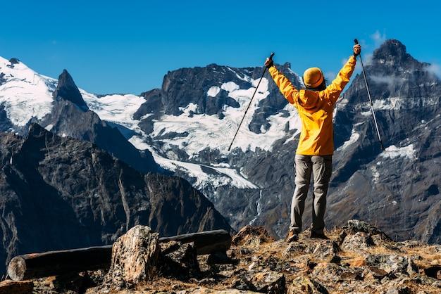 Kobieta podróżująca po kaukazie. sporty górskie. sportowiec szczęśliwy finisz. turystyka górska. piesza wycieczka. podróż w góry. nordic walking wśród gór. skopiuj miejsce