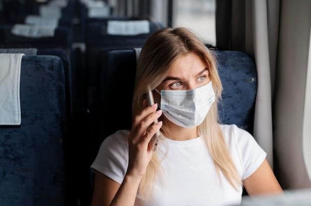 Kobieta podróżująca pociągiem i rozmawiająca przez telefon w masce medycznej