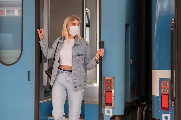 Kobieta podróżująca pociągiem nosząca maskę medyczną dla ochrony