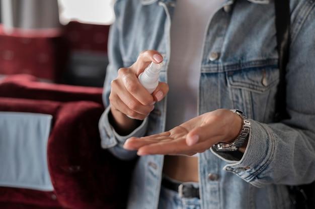 Kobieta podróżująca pociągiem za pomocą sprayu do dezynfekcji rąk w celu ochrony