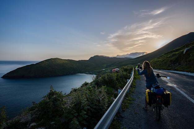 Kobieta podróżująca rowerzystka fotografująca owce i panoramiczne widoki na zatokę keem na wyspie achill w irlandii