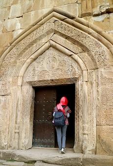 Kobieta podróżująca w nakryciu głowy w kościele wniebowzięcia nmp w zamku ananuri w stanie georgia