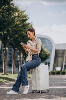 Kobieta podróżująca z bagażem na lotnisku i rozmawiająca przez telefon