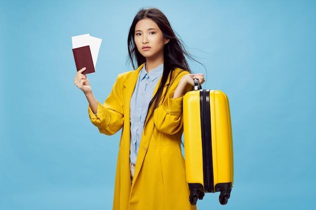 Kobieta podróżująca z żółtą walizką i biletami wizowymi paszportowymi