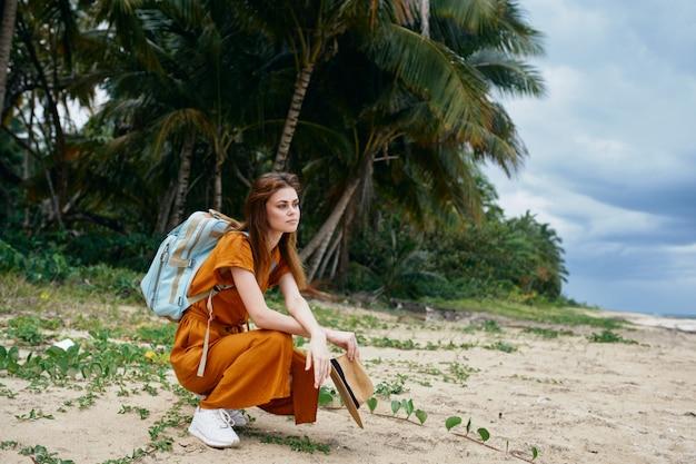 Kobieta podróżuje na wyspowym kapeluszu w ręku plecak na piasku na plecach