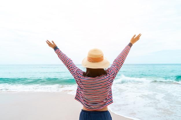 Kobieta podróżuje po całym świecie z letnią swobodą na plaży i relaksującym życiem.