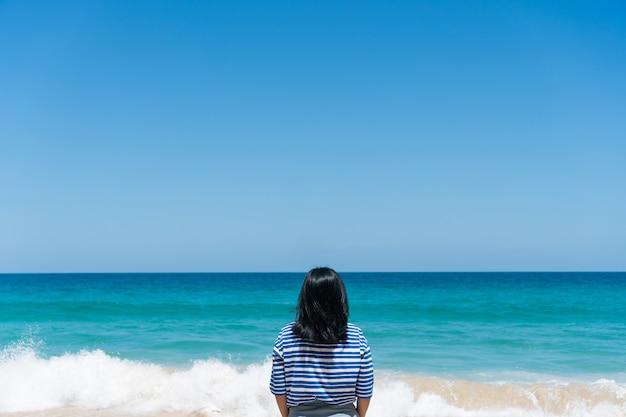 Kobieta podróżuje po całym świecie z letnią swobodą na plaży i relaksującym życiem