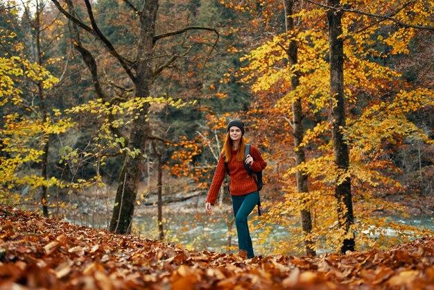 Kobieta podróżuje w lesie jesienią w krajobrazie przyrody żółte liście na drzewach turystyki