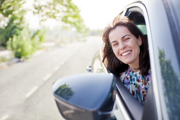 Kobieta podróżuje w samochodzie i patrzeje w zewnętrznym lustrze