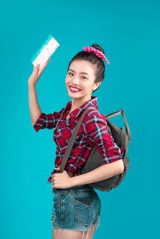 Kobieta podróży. młoda piękna azjatycka kobieta podróżnik z biletem lotniczym na niebieskim tle
