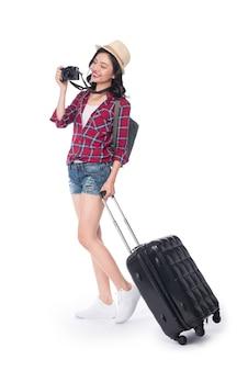 Kobieta podróży. młoda piękna azjatycka kobieta podróżnik z walizką i aparatem na białym tle