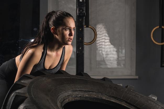 Kobieta podrzuca oponę na siłowni.