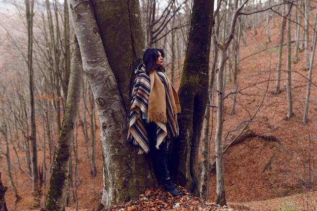 Kobieta podziwia jesienne widoki w zimny dzień do lasu