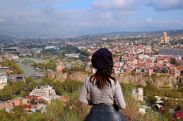 Kobieta podziwiać widok z lotu ptaka z wieloma charakterystycznymi zabytkami stolicy gruzji tbilisi