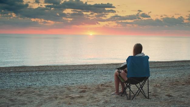 Kobieta, podziwiając zachód słońca nad morzem, siedząc w składanym fotelu turystycznym