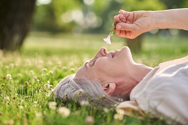 Kobieta podziwiająca kwiat leżący na trawie