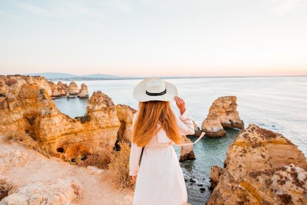 Kobieta podziwiająca wspaniały widok na skaliste wybrzeże podczas wschodu słońca w lagos na południu portugalii