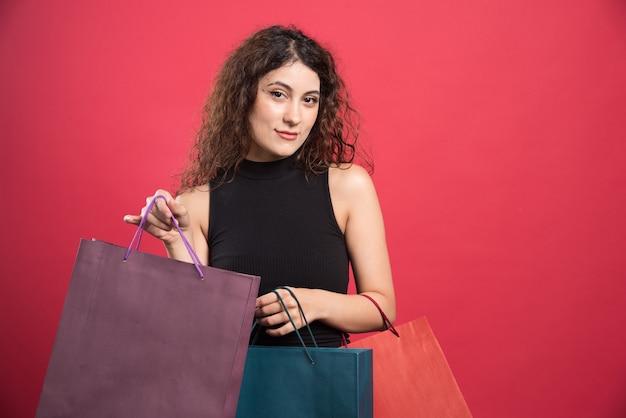 Kobieta pokazano jej nowe ubrania zakupu na czerwonym tle. wysokiej jakości zdjęcie