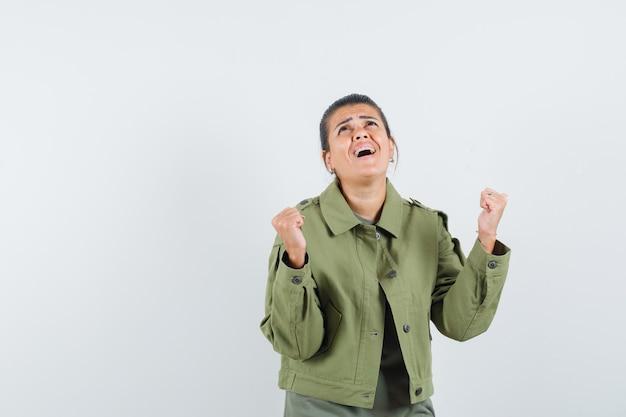 Kobieta pokazując gest zwycięzcy w kurtce, koszulce i patrząc szczęśliwy
