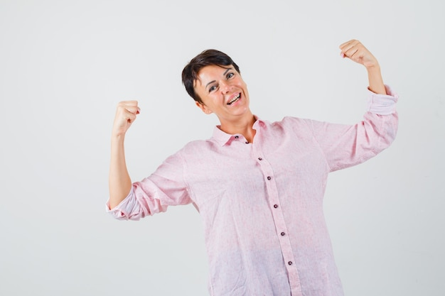 Kobieta pokazując gest zwycięzcy w różowej koszuli i patrząc na szczęście, widok z przodu.