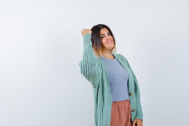 Kobieta pokazując gest zwycięzcy w ubranie i patrząc na szczęście, widok z przodu.