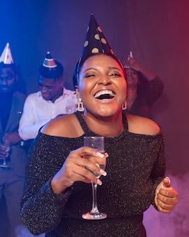Kobieta pokazując jej kieliszek do szampana i się śmieje