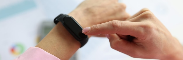 Kobieta pokazując palec na koncepcji zarządzania czarną bransoletką fitness zbliżenie