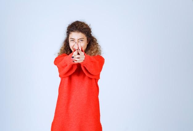 Kobieta pokazując pistolet znak w dłoni.